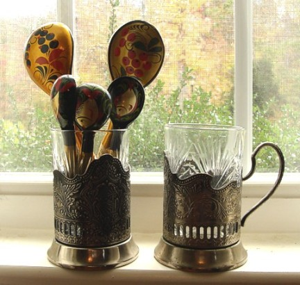 Silver-plated podstakanniki with cut-glass inserts, and a bouquet of lacquered wood spoons in traditional Russian patterns.