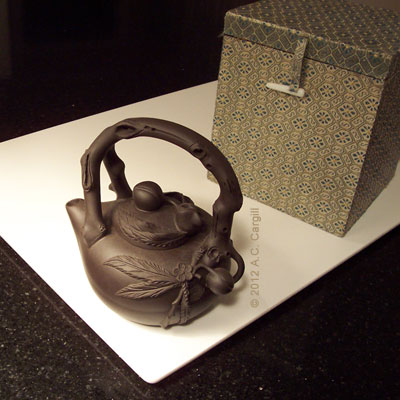 A peach-design Yixing teapot with brocade covered storage box