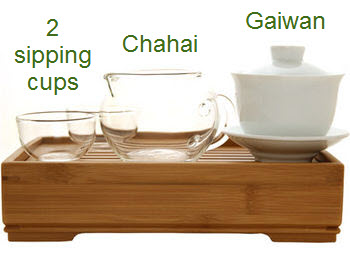 A tea set with a white gaiwan, a glass chahai, and 2 glass sipping cups on a bamboo tea tray