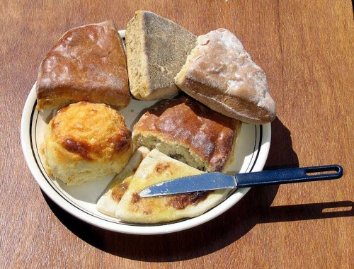 Clockwise from bottom: Hot buttered tattie scones next to a cheese scone, shiny and flat treacle scones, and a milk scone above a fruit scone. (source: Wikipedia)