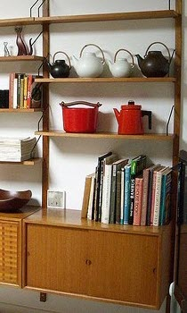 Mix it up by putting some teapots on a bookshelf along with some books. (stock image)